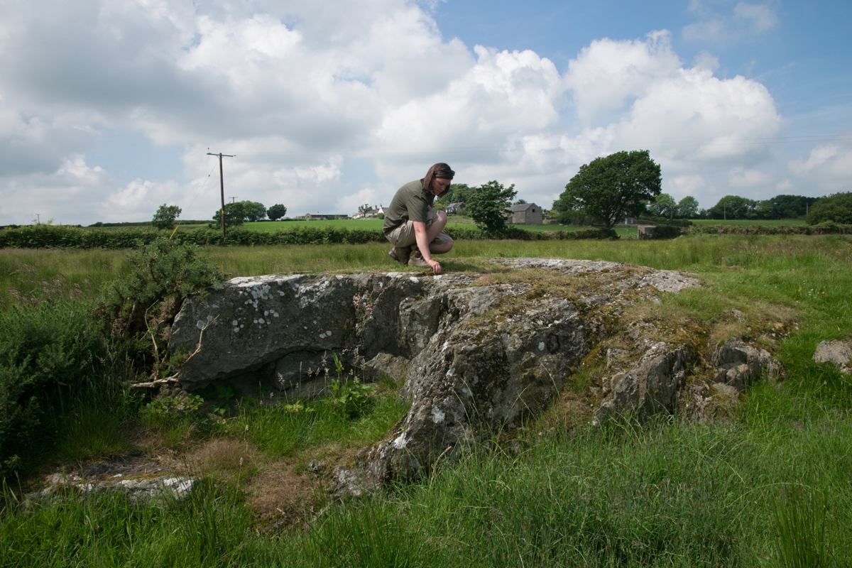 Dr Ffion Reynolds examining nearby outcrops for carved cupmarks. Anglesey, Wales